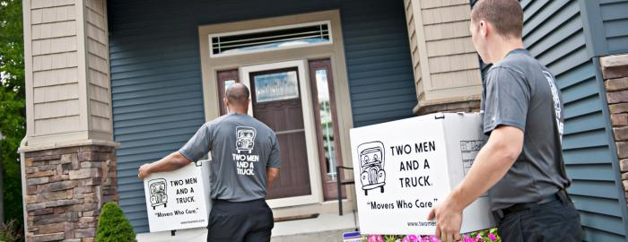 Movers carrying boxes into a home