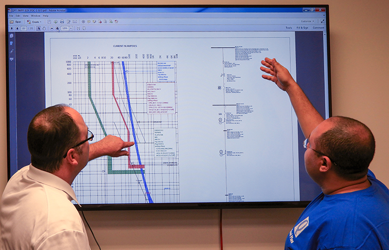 engineers review a power study for an industrial project