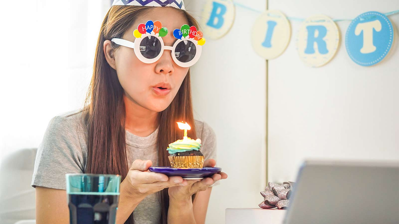 Woman blowing a candle in a cupcake