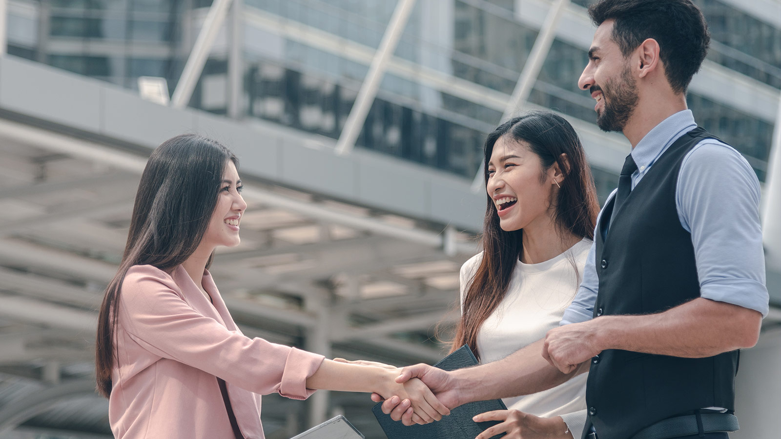 Three people while shaking hands