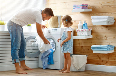 Happy family man father householder and child in laundry with