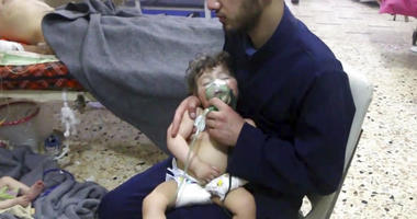 Medical worker in Syria giving toddler oxygen through respirator