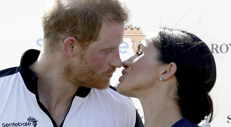 Meghan, Duchess of Sussex and Britain's Prince Harry kiss