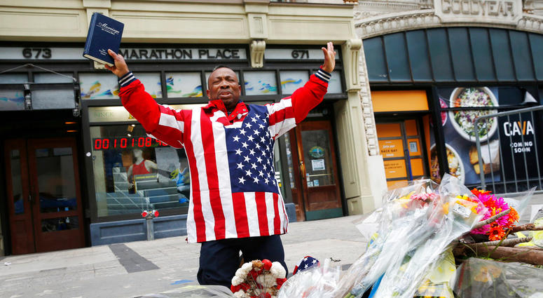 Cristopher Nzenwa, of Boston, prays at the site of the first explosion during the 2013 Boston Marathon