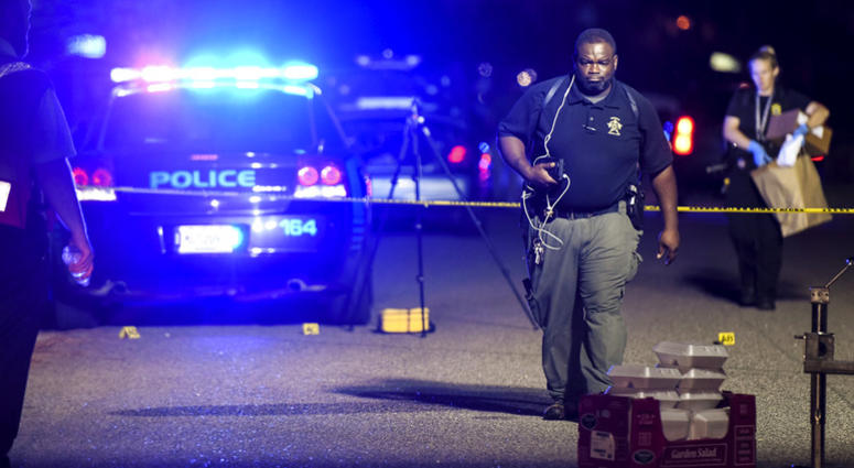A forensics team member exits the crime scene on Ashton Drive in the Vintage Place neighborhood where several members of law enforcement were shot, one fatally, Wednesday, Oct. 3, 2018, in Florence, S.C.
