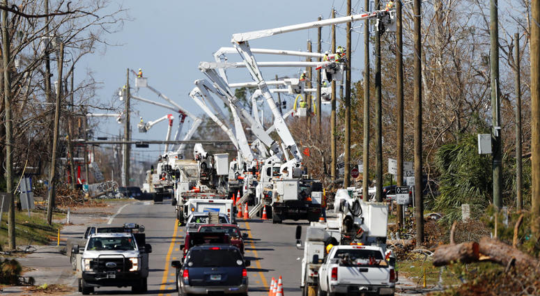 Utility crews set up new poles and utility wires in the aftermath of Hurricane Michael in Panama City, Fla