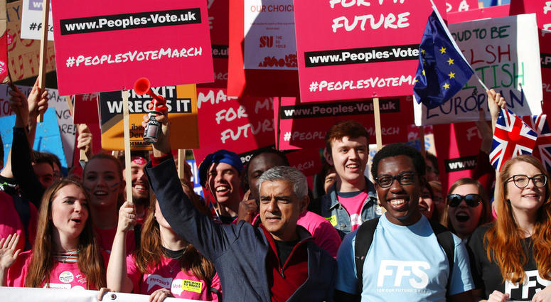 Mayor of London Sadiq Khan, front centre, holds a klaxon horn, as he joins protesters in the People's Vote March for the Future, in London, Saturday Oct. 20, 2018