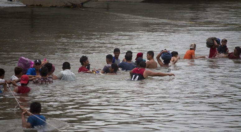 A group of Central American migrants wade across the Suchiate River, on the the border between Guatemala and Mexico