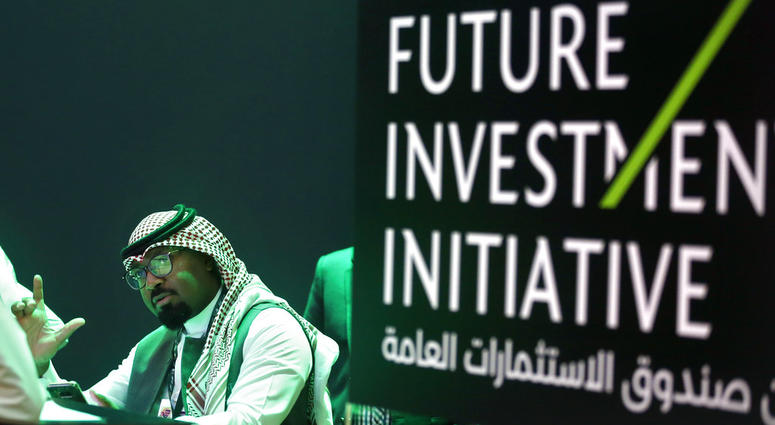 Saudi employees print badges of participants of the Future Investment Initiative conference, which kicks off Tuesday, in Riyadh, Saudi Arabia, Monday, Oct. 22, 2018.