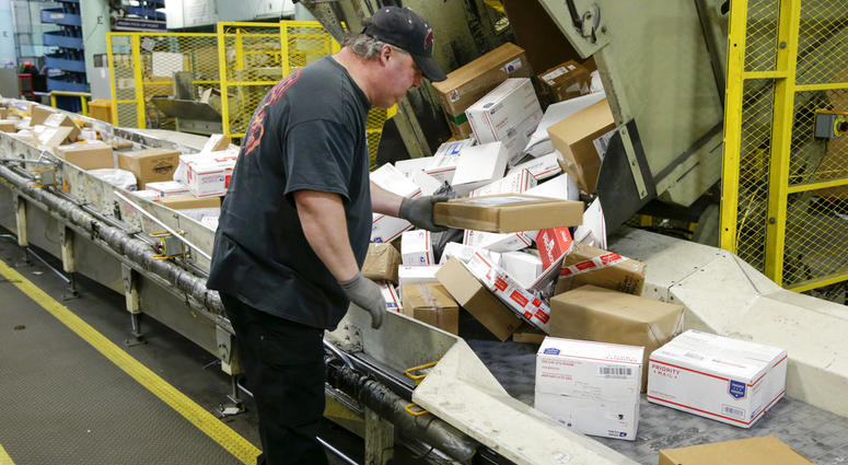 Steve Robino arranges packages on a conveyor belt at the main post office