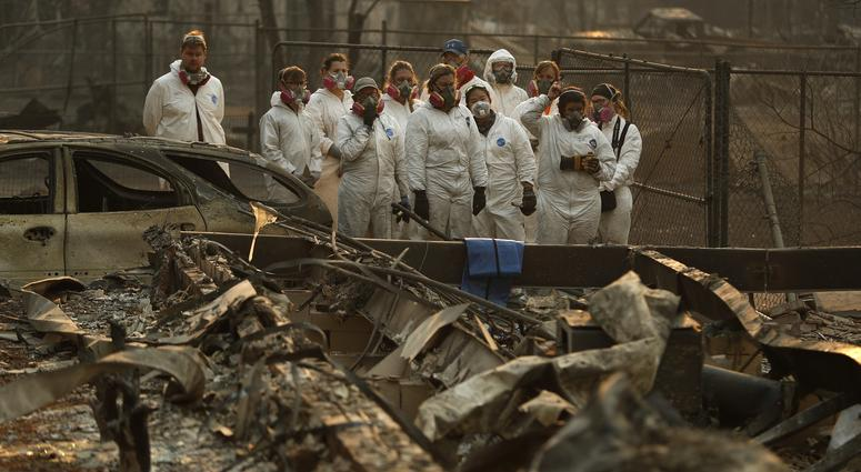 Anthropology students observe as human remains are recovered from a burned out home at the Camp Fire, Sunday, Nov. 11, 2018, in Paradise, Calif.