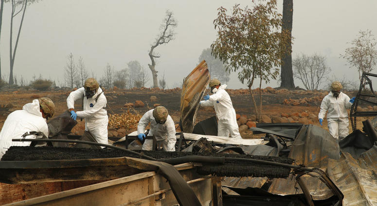 Members of the California Army National Guard search a property for human remains at a home burned in the Camp fire,