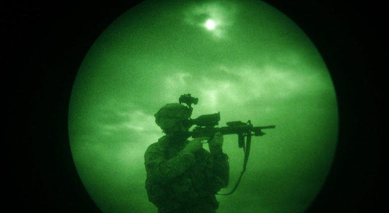U.S soldier looks through the scope of his weapon during a night patrol in Mandozai, in Khost province, Afghanistan