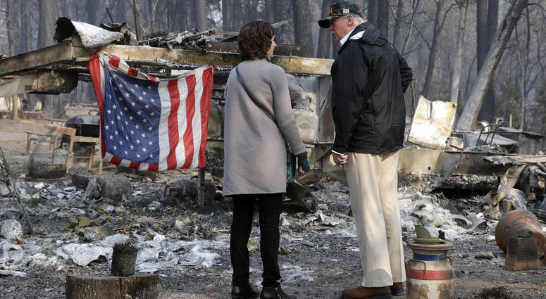 President Donald Trump talks to Mayor Jody Jones as he visits a neighborhood impacted by the wildfires, Saturday, Nov. 17, 2018, in Paradise, Calif.