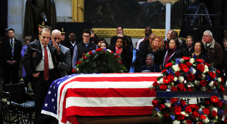 Former Sen. Bob Dole salutes the flag-draped casket containing the remains of former President George H.W. Bush as he lies in state at the U.S. Capitol in Washington