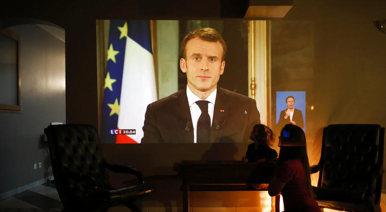 A woman and her daughter watch French President Emmanuel Macron during a televised address to the nation