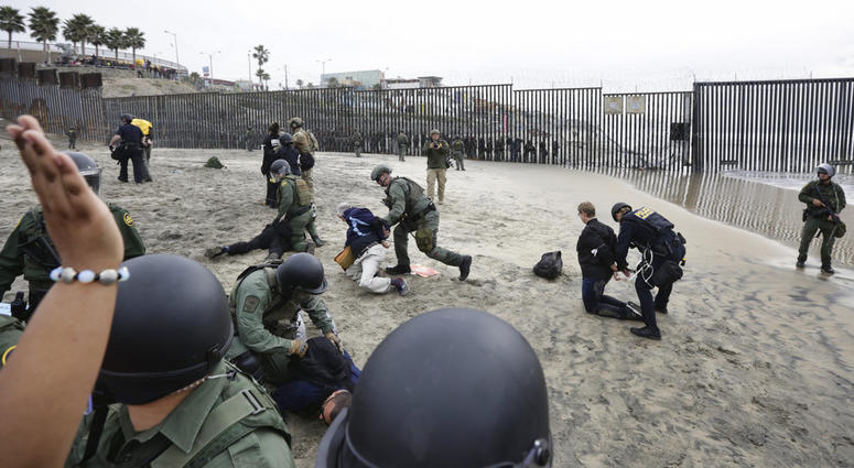 Immigrant rights activists are arrested by border patrol agents during a protest at the border wall in San Diego, Calif., Monday, Dec. 10, 2018. (