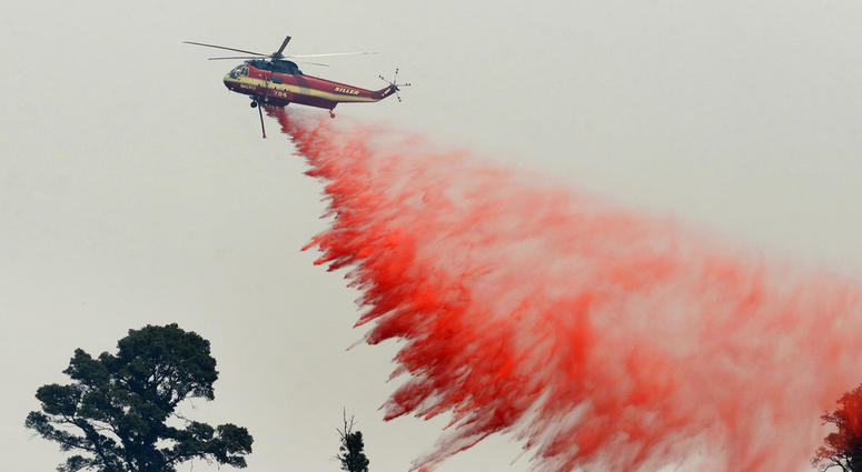 A fire attack helicopter makes a retardant drop during a firing operation