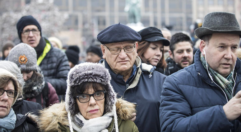 Residents react during a gathering in a central square of the eastern French city of Strasbourg, Sunday Dec.16, 2018 to pay homage to the victims of a gunman who killed four people and wounded a dozen more.