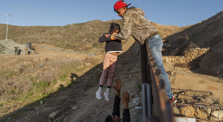 A migrant from Honduras pass a child to her father after he jumped the border fence to get into the U.S. side to San Diego, Calif., from Tijuana, Mexico