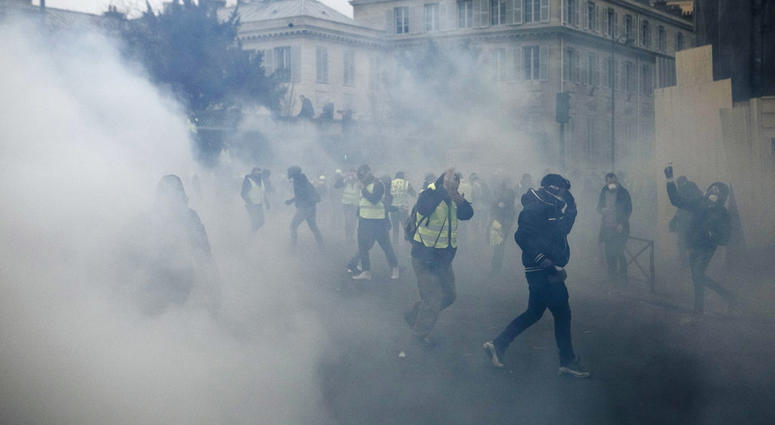 Demonstrators run as tear gas is thrown by riot police during a protest in Paris, Saturday, Jan. 5, 2019. Hundreds of protesters were trying to breathe new life into France's apparently waning yellow vest movement with marches in Paris and gatherings in o