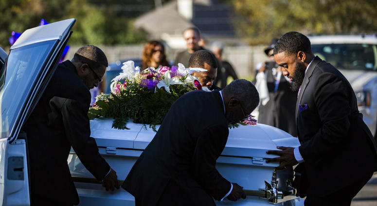 The casket of Jazmine Barnes is removed from the funeral hearse