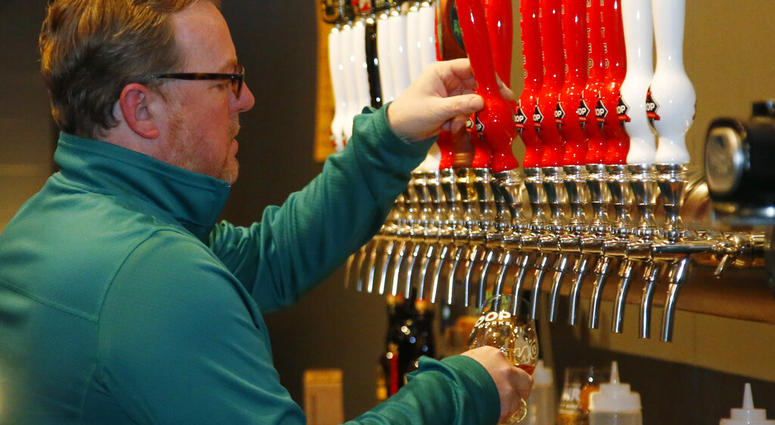 Sean Mossman, director of sales and marketing for COOP Ale Works, draws a beer in the COOP taproom in Oklahoma City