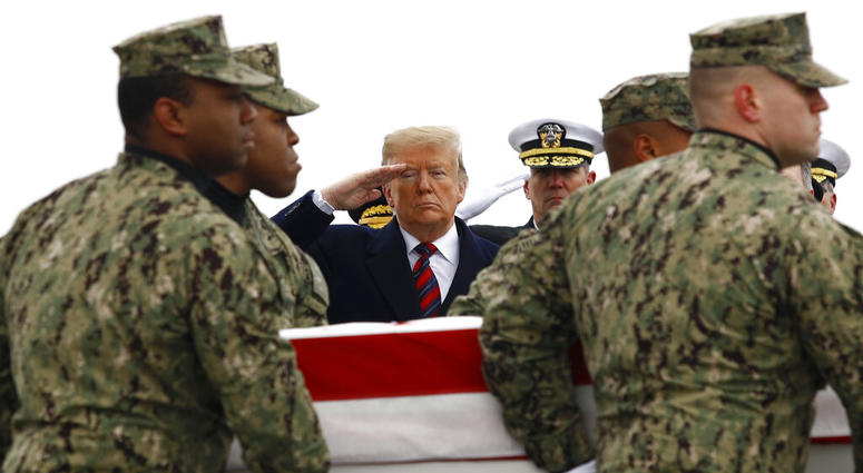 President Donald Trump salutes as a U.S. Navy carry team moves a transfer case containing the remains of Scott A. Wirtz, Saturday, Jan. 19, 2019, at Dover Air Force Base, Del