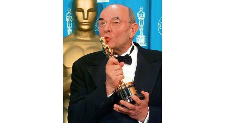 director Stanley Donen kisses the Oscar he received for Lifetime Achievement backstage at the 70th Academy Awards