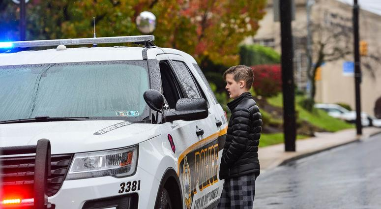 A young Squirrel Hill resident talks with police as the Tree of Life Synagogue sits in the background