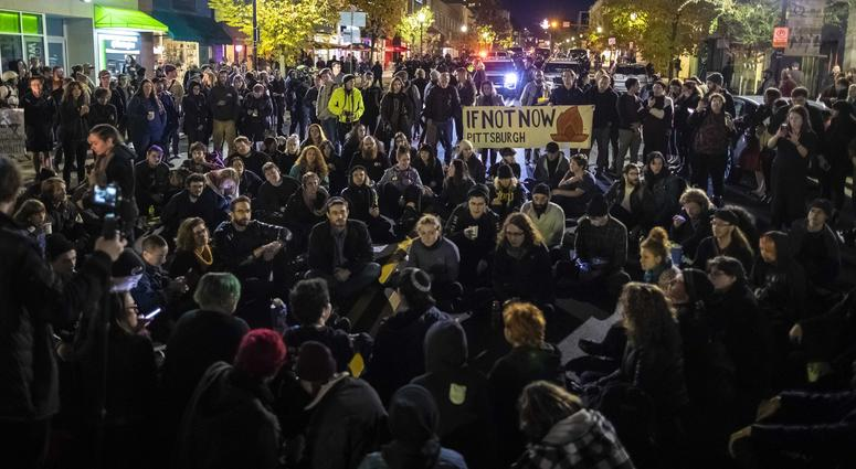 Protesters sit and sing Jewish songs in the middle of Forbes Ave. in Squirrel Hill