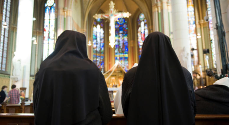 Two nuns are praying in a church