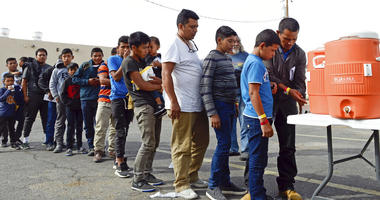 migrants wait in line to get drinks after being dropped off by the Border Patrol at the Gospel Rescue Mission in Las Cruces, N.M.