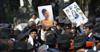 Relatives hold photographs of the victims at a mass funeral at the Holy Trinity Cathedral in Addis Ababa, Ethiopia Sunday, March 17, 2019.