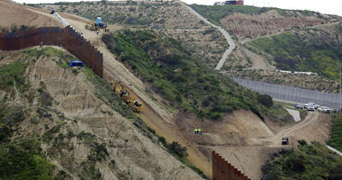 construction crews replace a section of the primary wall separating San Diego