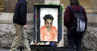 Passers-by looks at a memorial display with a drawing of Antwon Rose II in front of the Allegheny County courthouse on the second day of the trial for Michael Rosfeld, a former police officer in East Pittsburgh