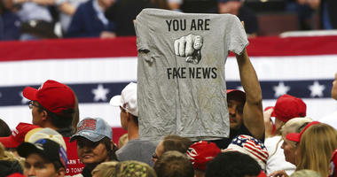 """a Trump supporter holds up a T-shirt reading """"You Are Fake News"""""""