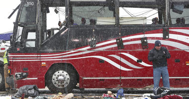 Debris litters the scene where a tour bus carrying passengers overturned just after midday