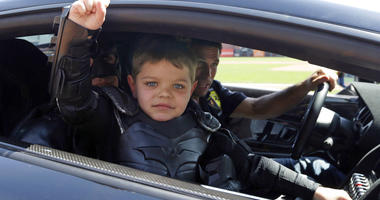 Miles Scott, dressed as Batkid, gestures as he sits in the Batmobile after throwing the ceremonial first pitch before a baseball game