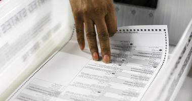 A Florida Elections Office staffer counts ballots during a manual recount