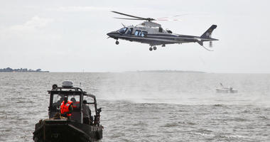 A helicopter searches for victims of a boat which capsized in Lake Victoria