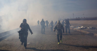 Migrants run from tear gas launched by U.S. agents