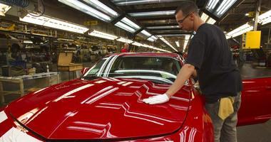 A worker checks the paint on a Camaro at the GM factory in Oshawa, Ontario
