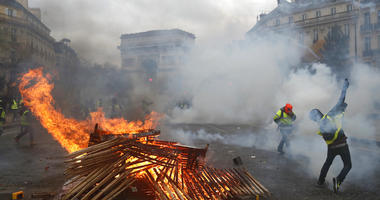Demonstrators run by a burning barricade near the Arc de Triomphe during a demonstration