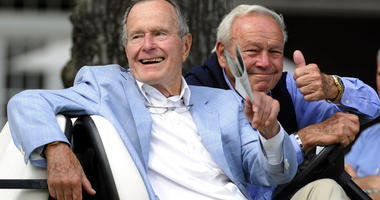 Former President George H. W. Bush, left, and golfing great Arnold Palmer acknowledge the gallery at the Champions Tour golf tournament in The Woodlands, Texas