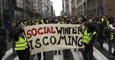 Protestors hold a banner which reads 'social winter is coming' during a demonstration in Brussels, Saturday, Dec. 8, 2018.