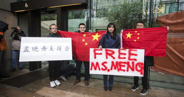 Supporters hold signs and Chinese flags outside British Columbia Supreme Court during the third day of a bail hearing for Meng Wanzhou, the chief financial officer of Huawei Technologies, in Vancouver, on Tuesday December 11, 2018.