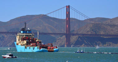 a ship tows The Ocean Cleanup's first buoyant trash-collecting device toward the Golden Gate Bridge in San Francisco en route to the Pacific Ocean.