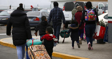 Migrants who have been a turn for an interview to request U.S. asylum walk to the El Chaparral pedestrian border crossing in Tijuana, Mexico, Friday, Dec. 21, 2018.
