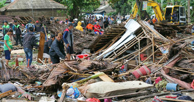 Residents inspect a house damaged by a tsunami, in Carita, Indonesia